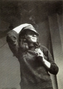 black and white photograph of bernice vincent taken by her husband don vincent in the early 70s. she is wearing a loose wool sweater and is tipping her hat with her right hand. in her left hand is a cigarette. she is smiling coyly off to the right of the frame.