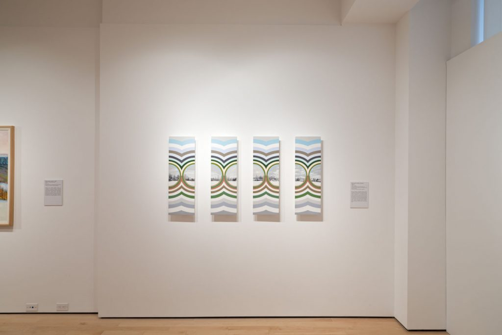 image of the painting Winter Seen by Bernice Vincent in an exhibition at Woodstock Art Gallery. It is a painting in four panels. Each panel shows one quater of a small, realist winter landscape. Each quater is split in two round sections that abut each other back to back. Each section is within a tall, slim, colourful, curved, geometric grid that draws its colours from the palatte of the landscape.
