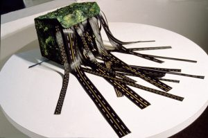 image of Bernice Vincent's ribbon box, a sculptural work in which a small folded box made from cardboard is painted with textured green to look like a landscape. ribbons of paper painted to look like roadways spill out from the open box lid.